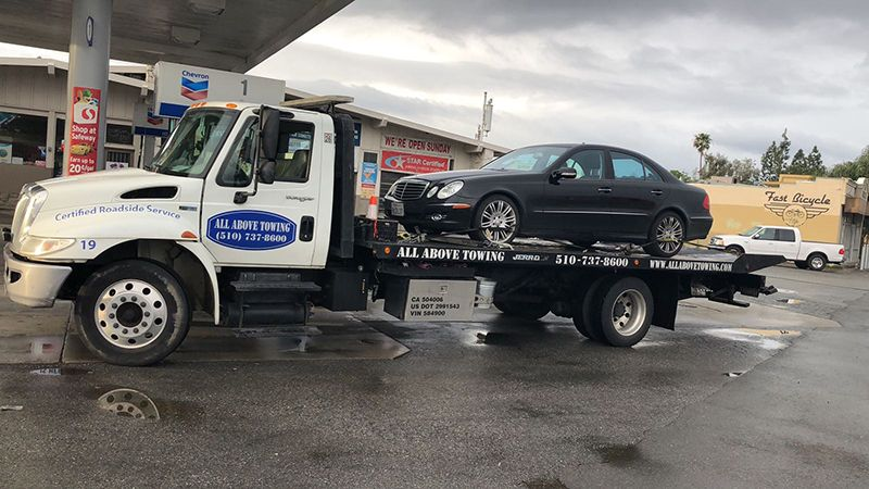 Image of Towing truch with a black car,ALL Above Towing LLC,Tow Truck Company